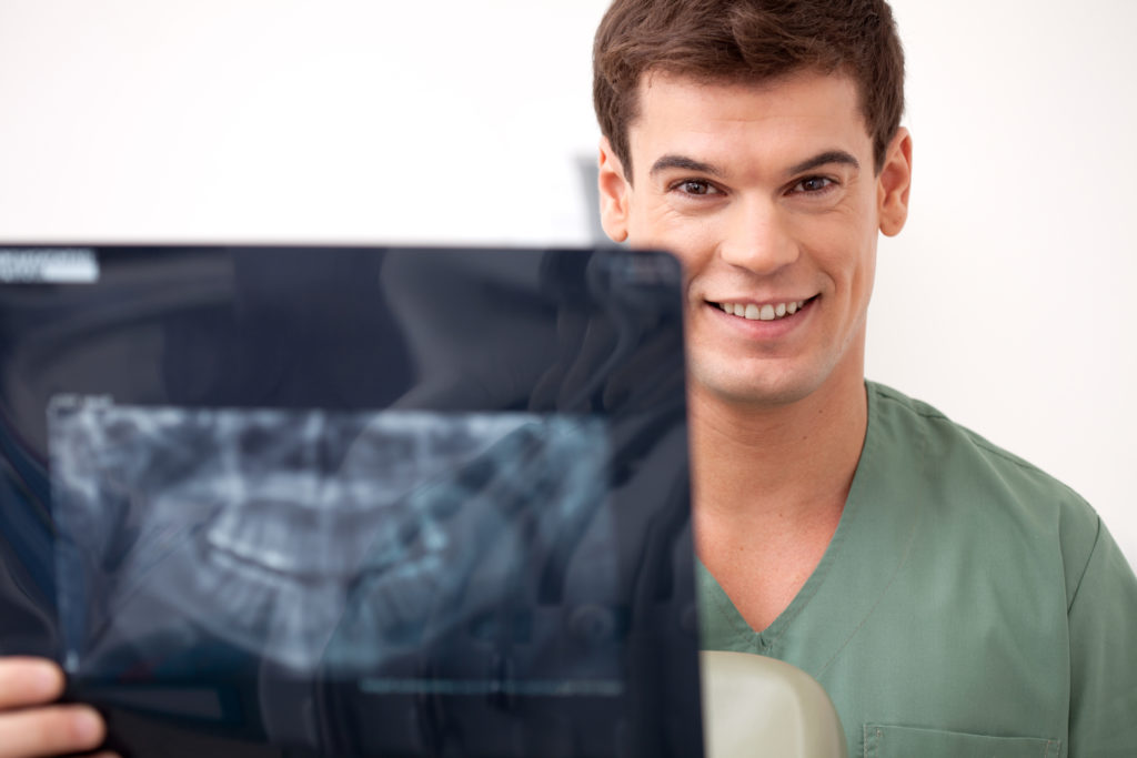 Young happy man dentist smiling looking at the camera holding an x-ray